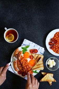 Weibliche hände, während sie englisches frühstück mit gebratenen würstchen, bohnen, pilzen, spiegeleiern, gegrillten tomaten hat. serviert mit einer tasse tee mit zitrone, toastbrot und butter. schwarzer hintergrund