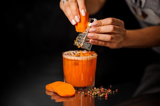 Weibliche hände, welche die karotten in das gesunde cocktail mit pfeffer zerreiben