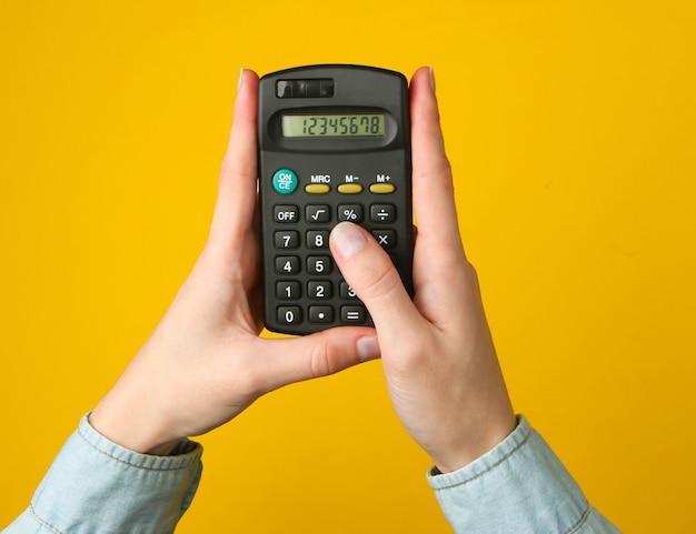 Weibliche hände zählen rechner auf einem gelben.