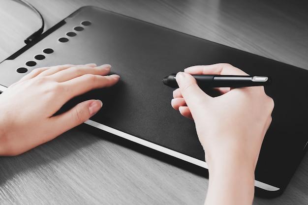 Weibliche hände zeichnen auf eine grafiktablette. designerhand hält einen stift und zeichnet auf eine tablette