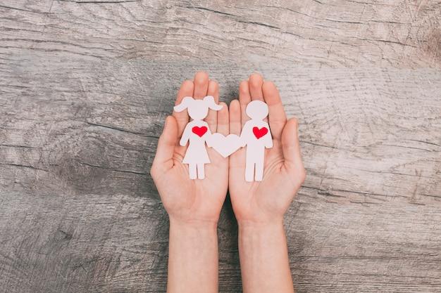 Weibliche hände zeigen zwei papierleute, einen mann und eine frau, auf einem hölzernen hintergrund