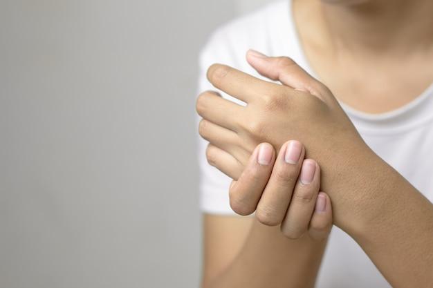 Weibliche haltene hand zur stelle der schmerzhand.