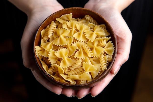 Weibliche halteplatte der draufsicht mit rohen gelben nudelnahrungsmahlzeit-italienischen nudeln