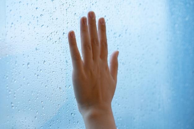 Weibliche hand am fenster während des regens. glas in wassertropfen.