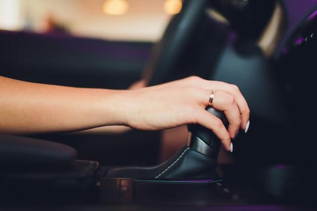 Weibliche hand auf automatikgetriebehebel