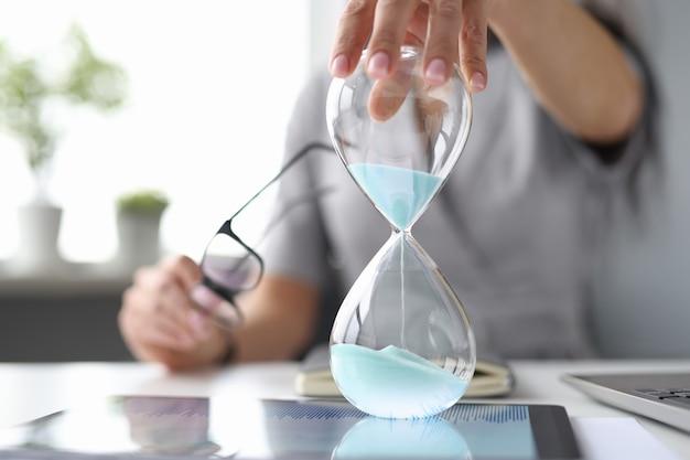 Weibliche hand auf dem desktop hält ein sanduhr-zeitmanagement im geschäftskonzept