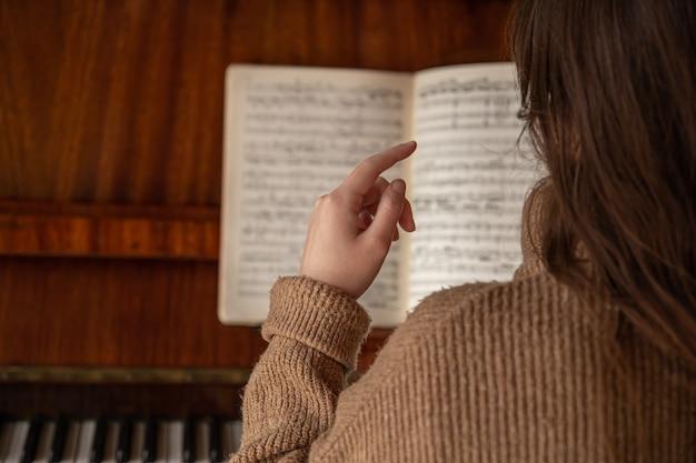 Weibliche hand auf einem unscharfen hintergrund von musiknoten auf dem klavier