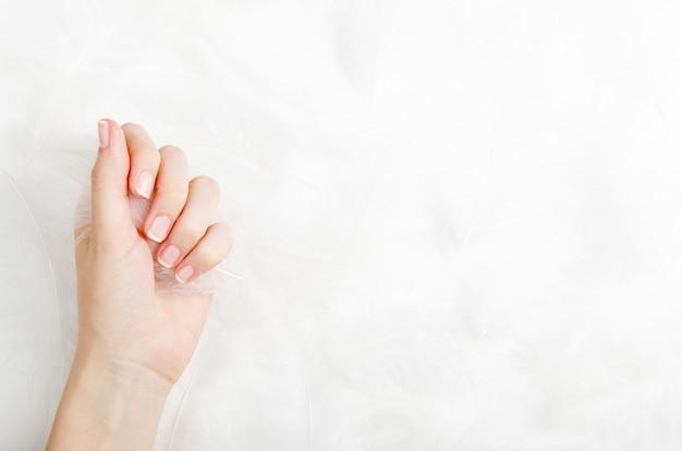 Weibliche hand auf einem weißen hintergrund mit federn.
