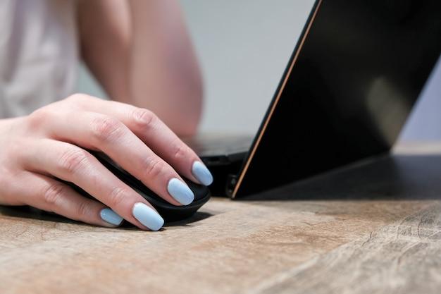 Weibliche hand auf einer computermaus auf laptophintergrund