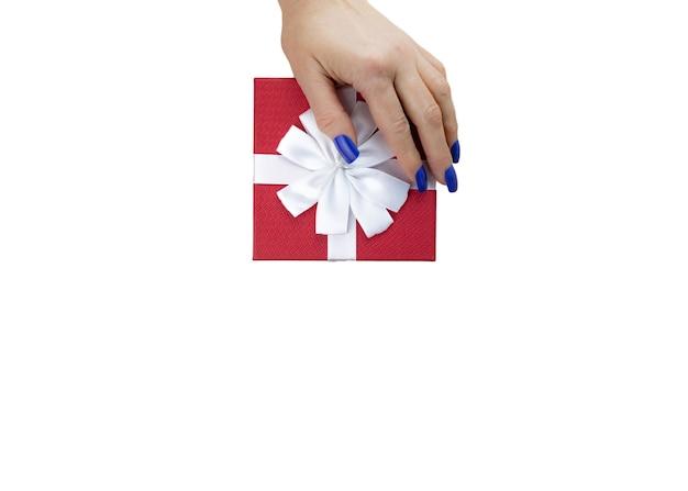 Weibliche hand auf geschenkbox rote farbe mit weißem band lokalisiert auf weißem tisch. nahansicht. selektiver weichzeichner. draufsicht. textkopierplatz.