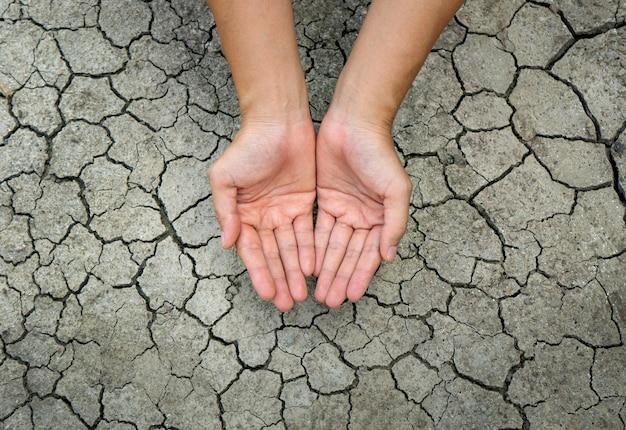 Weibliche hand auf trockenem, rissigem boden