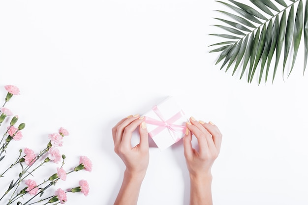 Weibliche hand band bogen auf dem kasten mit einem geschenk