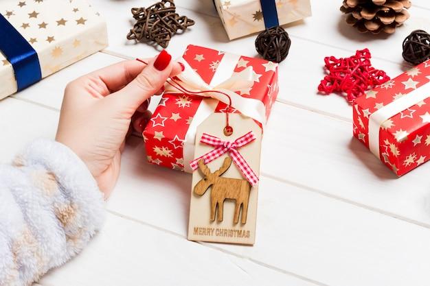 Weibliche hand der draufsicht binden geschenk des neuen jahres auf festlichem hölzernem. weihnachtszeit
