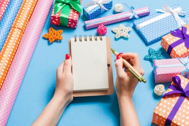 Weibliche hand der draufsicht, die einige anmerkungen im noteebok auf blau macht. neujahrsdekorationen und spielzeug. weihnachtszeit
