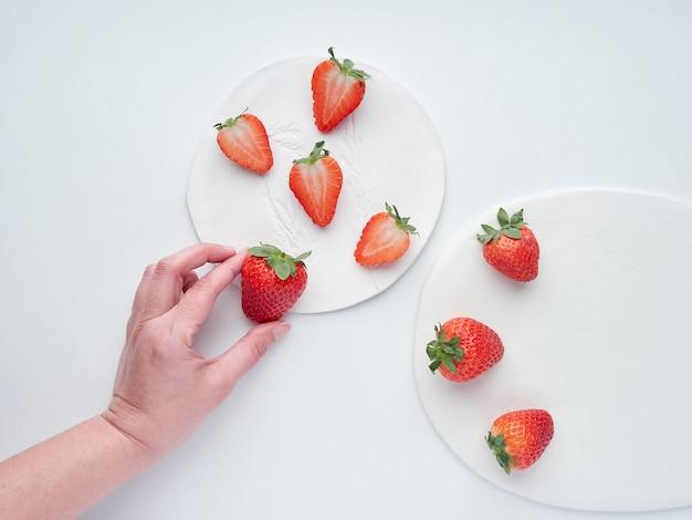 Weibliche hand der erdbeeren, die eine erdbeere auf einer flachen laienzusammensetzung pflücken