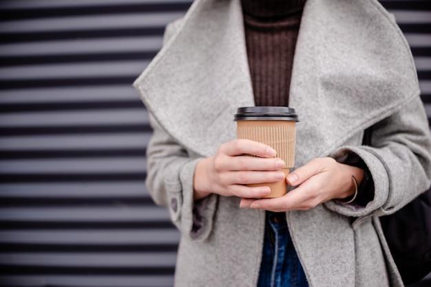 Weibliche hand der frau mit kaffeetassepapier latte.