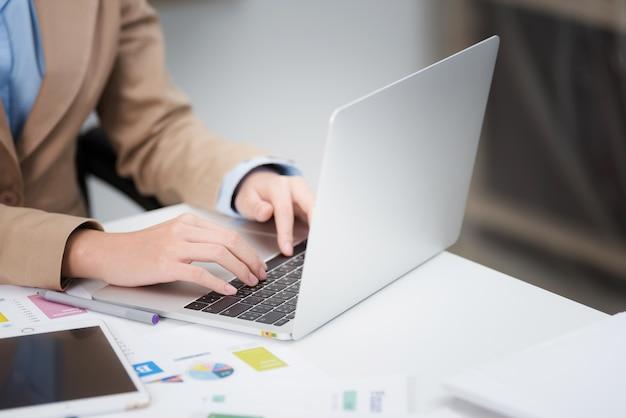 Weibliche hand der nahaufnahme, die auf laptoptastatur im büro schreibt