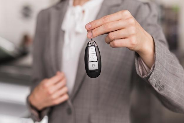 Weibliche hand der nahaufnahme, die autoschlüssel hält