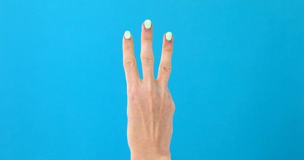 Weibliche hand der nahaufnahme, die von 3 zählt