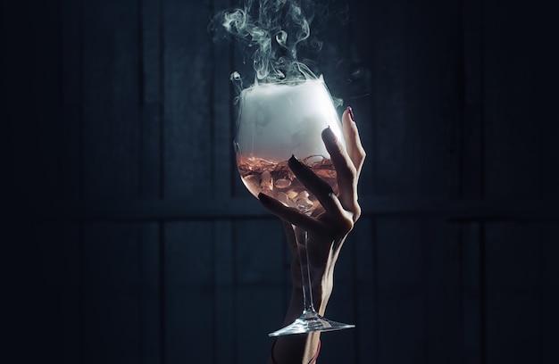 Weibliche hand der nahaufnahme, die weinglas des geheimnisvollen weißen kristallinen materials der flüssigkeit mit schaum auf hölzerner dunkelheit hält