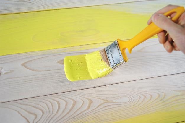 Weibliche hand der nahaufnahme mit dem pinsel, der eine natürliche holztür mit gelber farbe malt. das konzept der farbigen, hellen, kreativen innenarchitektur für eine junge familie. so malen sie eine holzoberfläche.