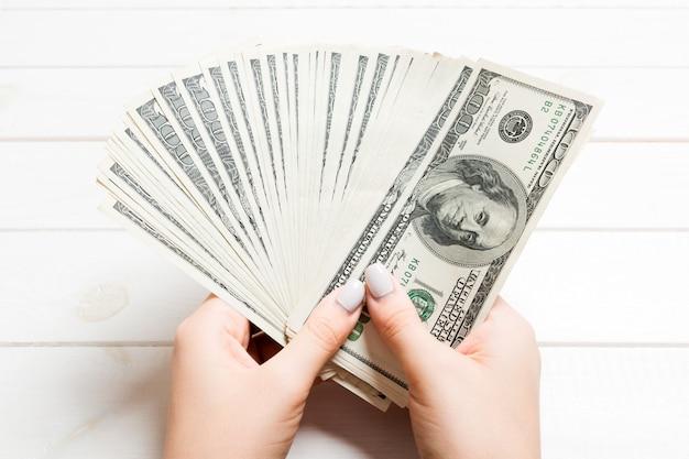 Weibliche hand der perspektivenansicht, die ein fangeld auf hölzernem hält. einhundert dollarnoten. kredit und schulden