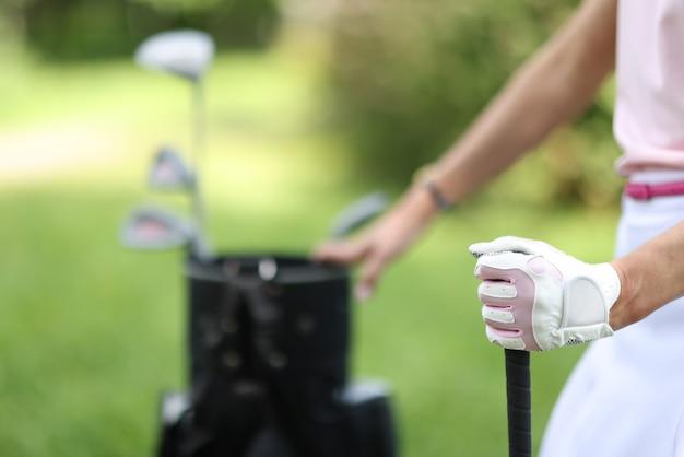 Weibliche hand des golfers im handschuh hält tasche mit golfschlägern