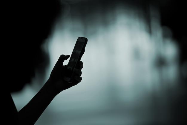 Weibliche hand des schattenbildes, die mobieltelefon hält.