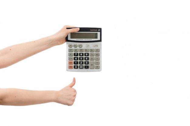 Weibliche hand des taschenrechners der vorderansicht, die wie zeichen auf dem weiß zeigt