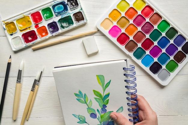 Weibliche hand, die aquarellmalerei des blaubeerzweigs skizziert. aquarellfarben und pinsel, draufsicht. kreative künstlerische wohnung lag.
