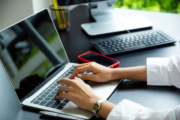 Weibliche hand, die auf tastatur des laptops schreibt