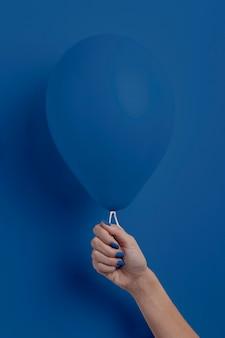 Weibliche hand, die ballon hält
