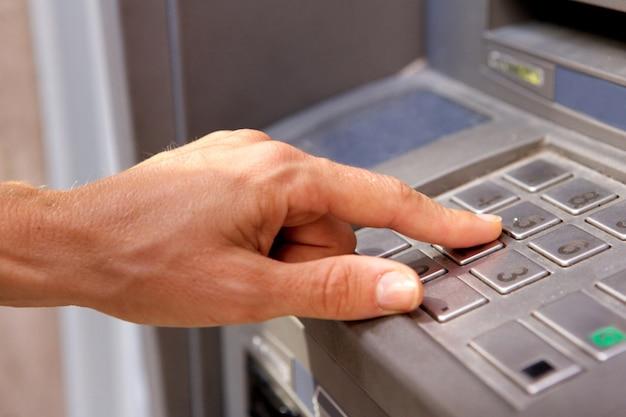 Weibliche hand, die bankmaschinen-tastatur verwendet
