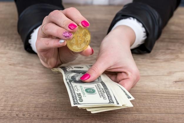 Weibliche hand, die bitcoin zeigt und dollarnoten hält