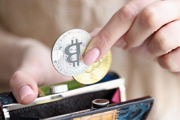 Weibliche hand, die bitcoins in brieftaschen-nahaufnahme setzt