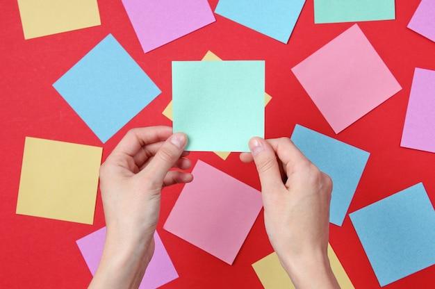 Weibliche hand, die blaues memoblattpapier auf rot unter vielen farbigen papierbögen hält