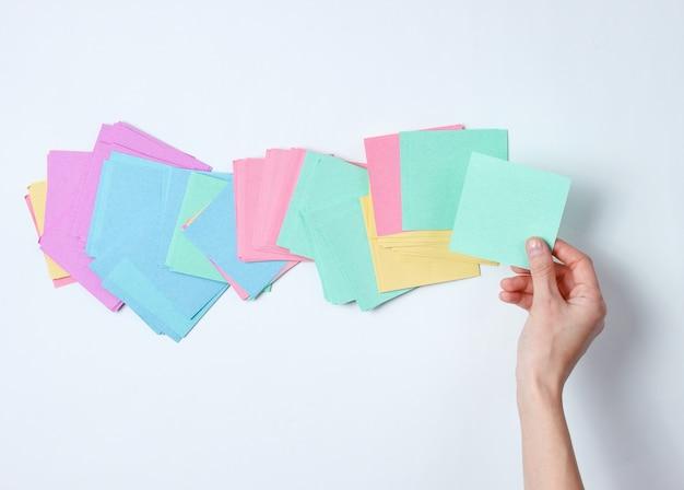 Weibliche hand, die blaues notizblatt des papiers auf weiß hält. draufsicht