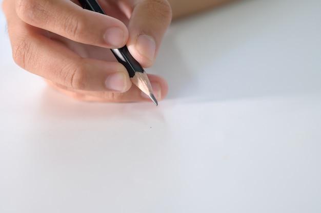 Weibliche hand, die bleistift auf weißem papierblatt hält