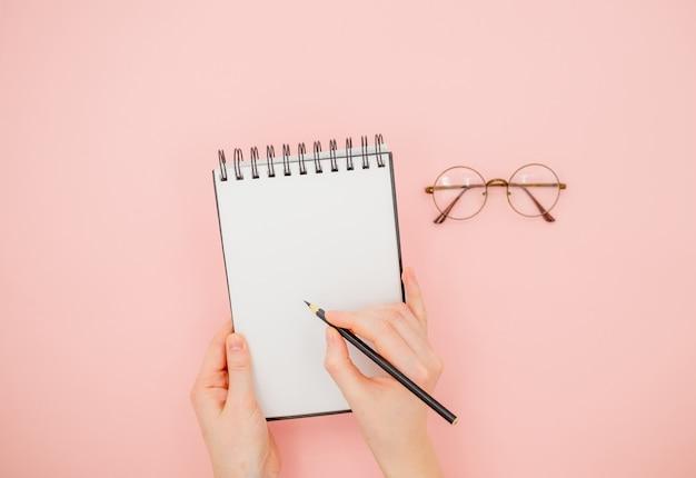 Weibliche hand, die bleistift und sketchbook hält.