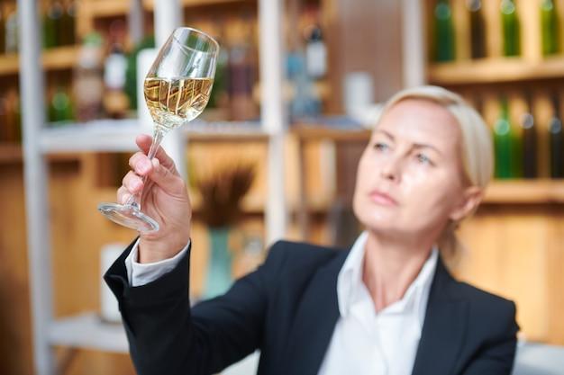 Weibliche hand, die bokal mit weißwein hält, während seine farbe und andere eigenschaften untersucht