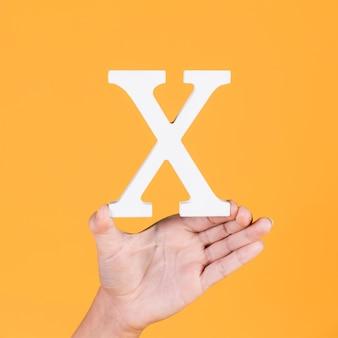 Weibliche hand, die das weiße alphabet x zeigt