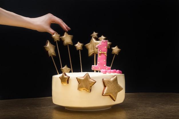 Weibliche hand, die dekorationen auf einem geburtstagskuchen mit dem rosa der nr. 1 und den goldsternen des lebkuchens korrigiert