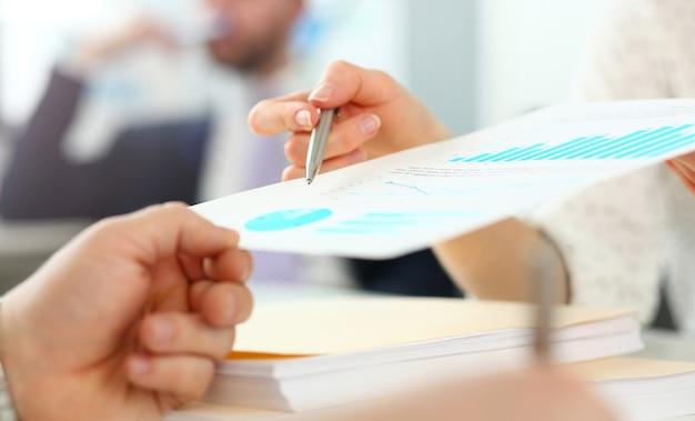Weibliche hand, die dem kunden finanzberichtspapier zeigt