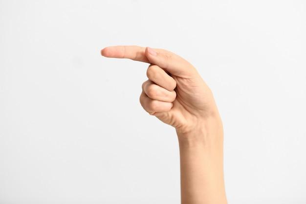 Weibliche hand, die den buchstaben g auf grau zeigt