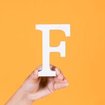 Weibliche hand, die den großbuchstaben f hält