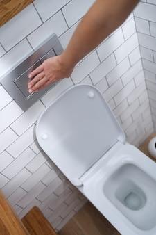 Weibliche hand, die den knopf für die toilettenspülung in der toiletten-nahaufnahme drückt