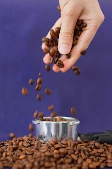 Weibliche hand, die die kaffeebohnen in den kaffee-manipulator auf der violetten oberfläche gießt
