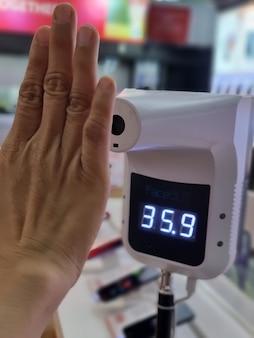 Weibliche hand, die die körpertemperatur mit einem digitalen infrarot-thermometer mit seinen händen überprüft