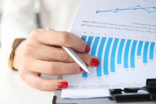 Weibliche hand, die dokumente mit graphen auf nahaufnahme der zwischenablage blättert