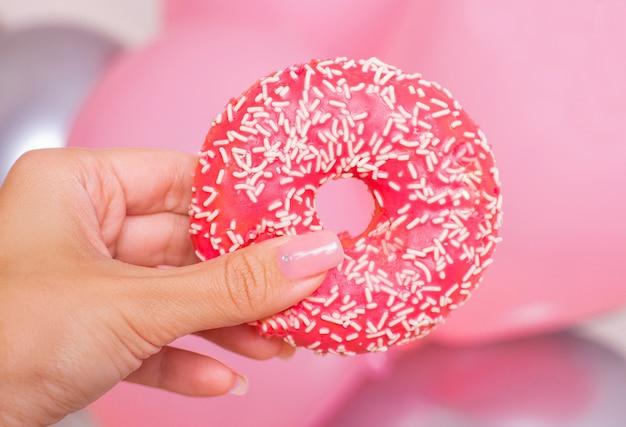 Weibliche hand, die donut hält